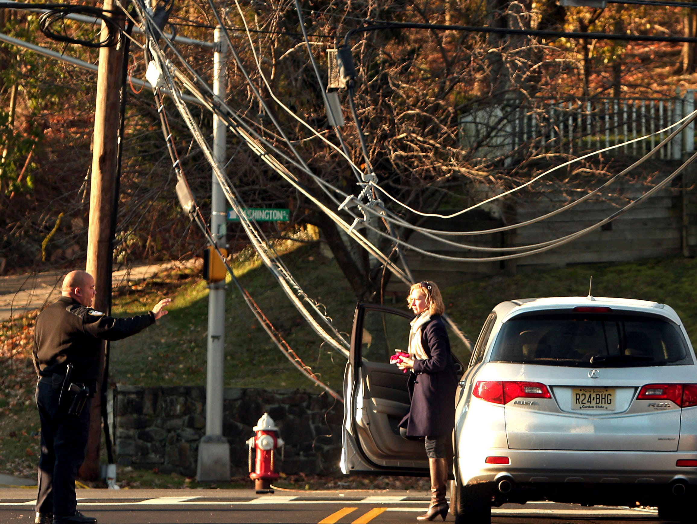 Morristown, N.J.- November 6, 2012-- A Morristown Police Officer talks to a woman carefully exiting her car after an early morning accident that left two cars draped in power lines on Washington Street in Morristown.