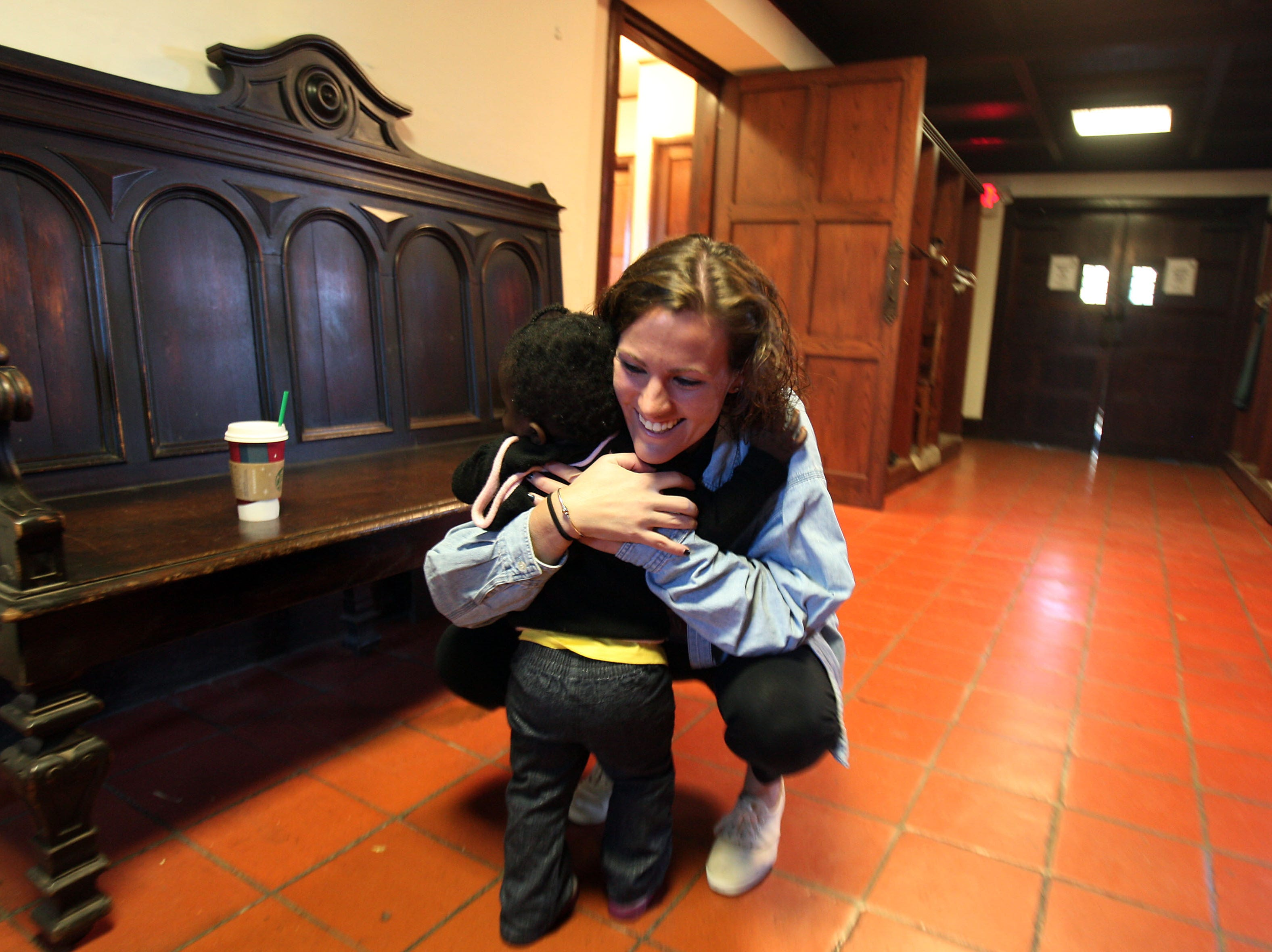 Morristown, N.J.- November 4, 2012--15-month-old Za'Inah Tolliver of Morristown, NJ gets a comforting hug from volunteer Caitlin Lynch of Randolph during breakfast offered by St Peter's Episcopal Church in Morristown, NJ as locals continue the recovery process in the aftermath of Hurricane Sandy.