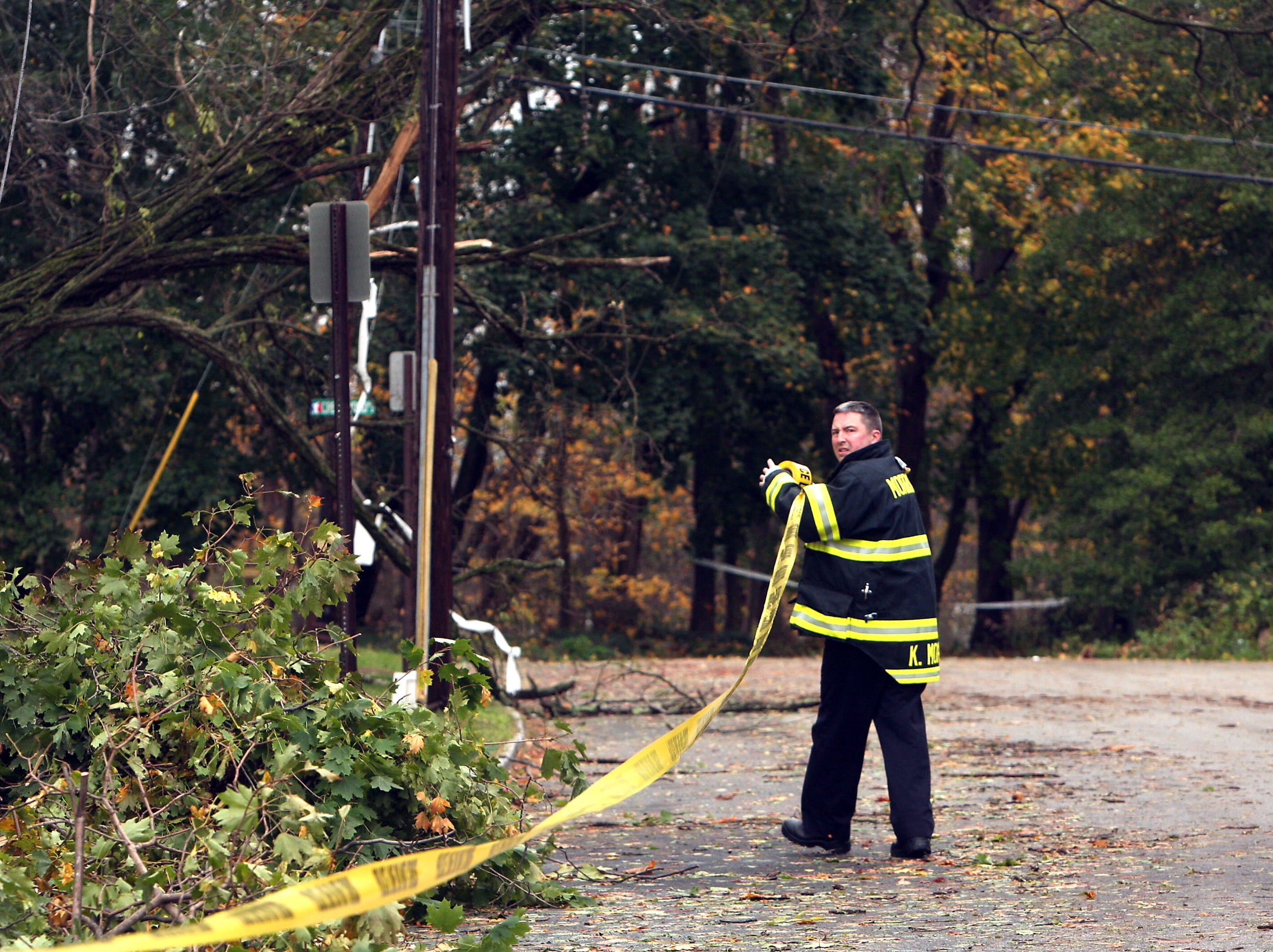 Morristown, NJ-- October 31, 2012--A Morristown Firefighter puts up emergency tape on Glenwood Road in Morristown, NJ in the aftermath of Hurricane Sandy. 