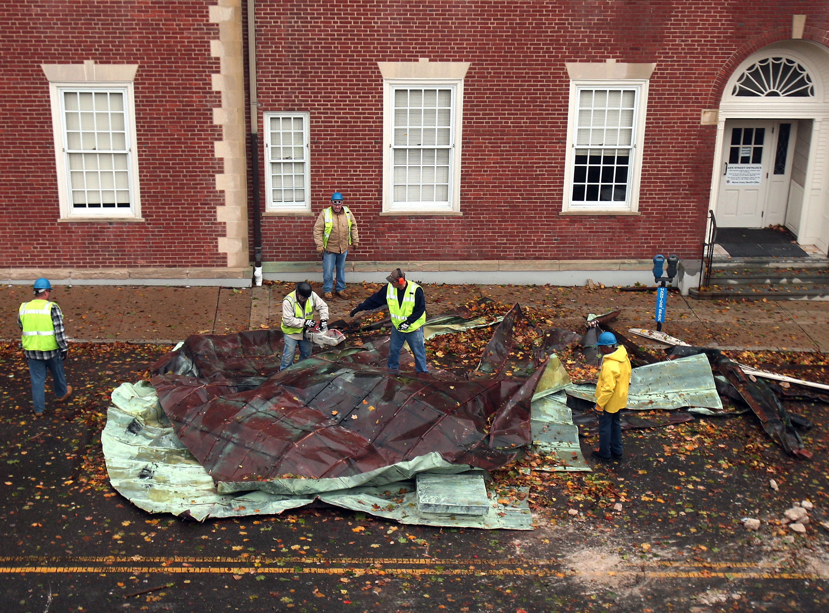 Morristown, NJ-- October 30, 2012--County grounds workers clean up after copper roofing from the Morris County Courthouse was blown off the roof due to heavy winds from Hurricane Sandy. 