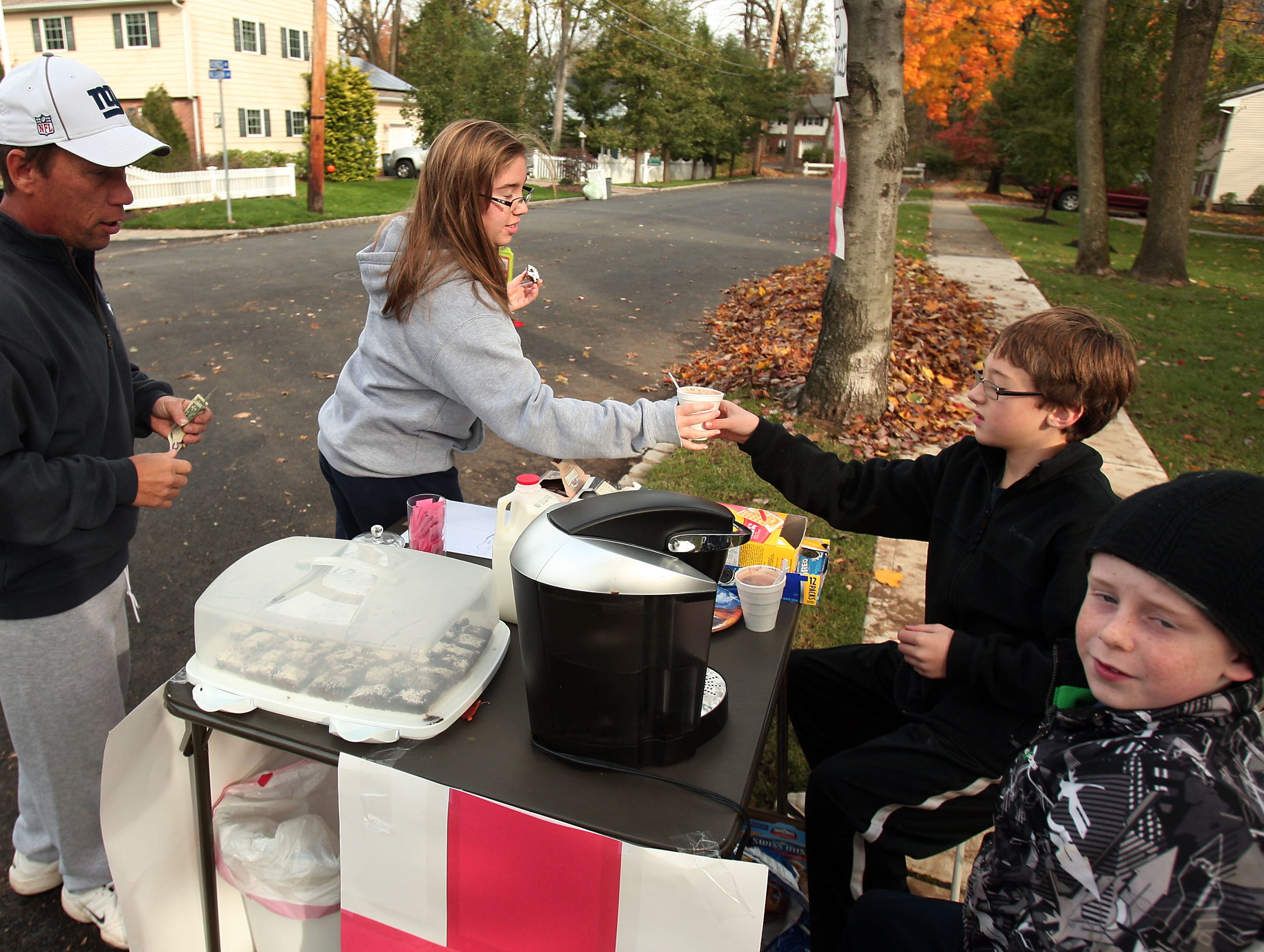 Chatham, NJ- November 1, 2012--Ron and Kelly Krincek of Chatham, NJ buy some hot chocolate from Nick Meyer (11) and Jack Konrad (8) who are taking the money for donations to the Red Cross on Hedges Avenue as locals continue the recovery process after Hurricane Sandy devastated the eastern seaboard.