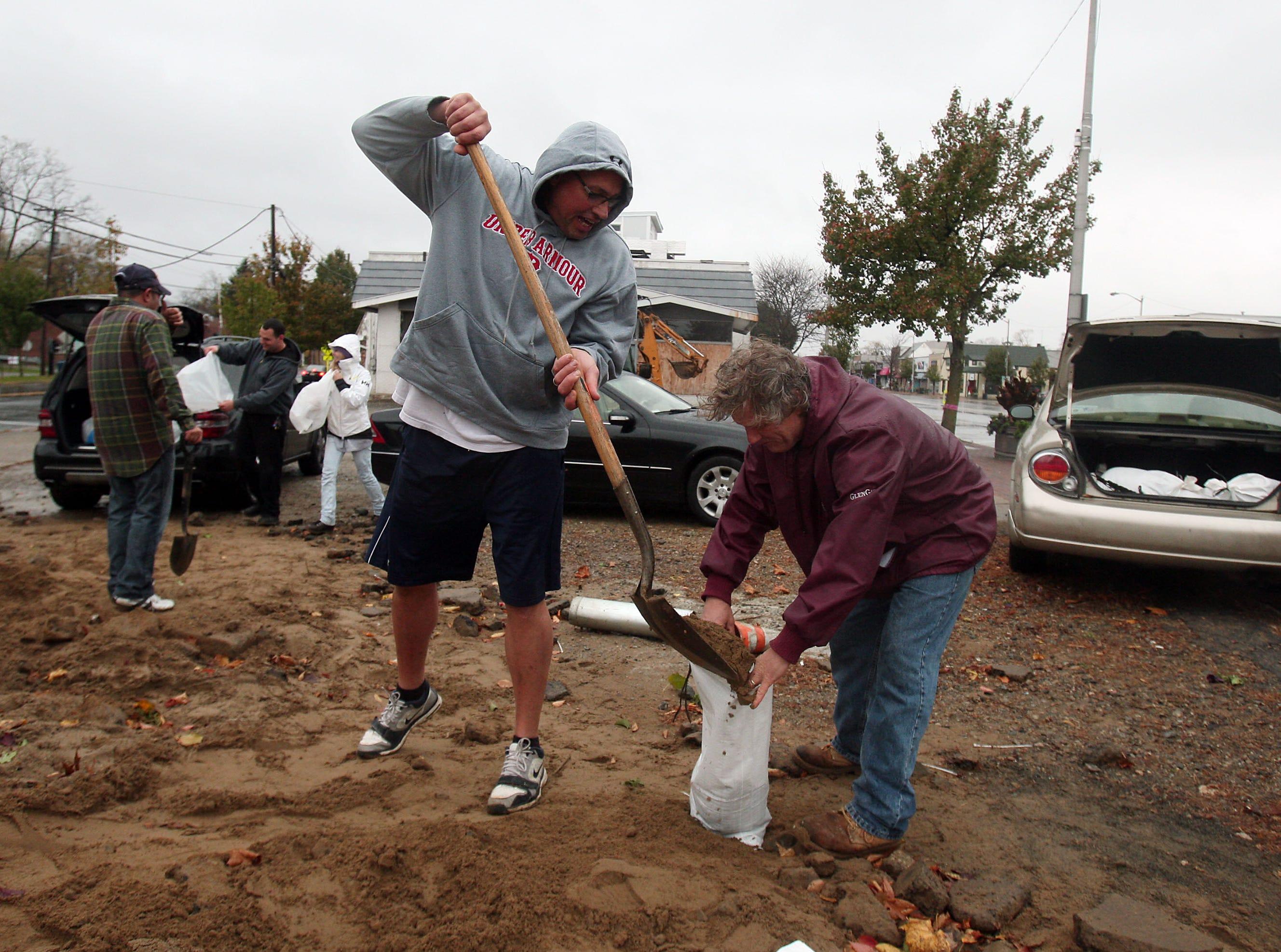 Denville,NJ-- October 29, 2012--Bill Schicke of Denville, NJ , l, and Jeff Sintic of Denville, NJ fill up sandbags in downtown Denville, NJ in preparation for Hurricane Sandy's approach.Bob Karp/Staff Photographer/DAILY RECORD