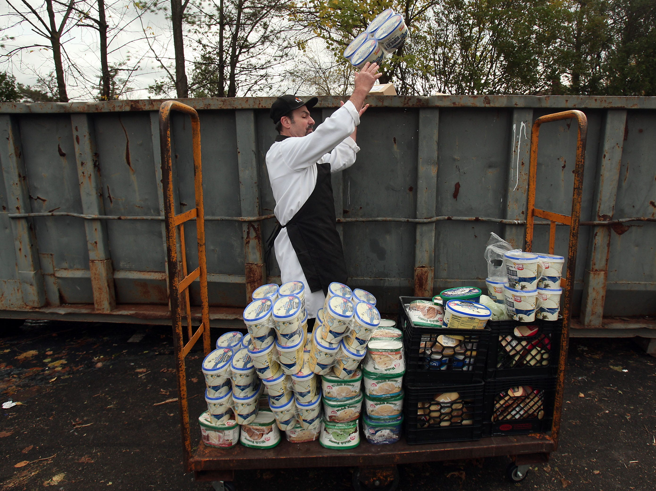 Chatham, NJ- November 1, 2012--Meat Manager B.B. O'Hara of Lake Parsippany, NJ throws perishables into a dumpster at Kings in Chatham, NJ after the supermarket lost most of its power after Hurricane Sandy devastated the eastern seaboard.