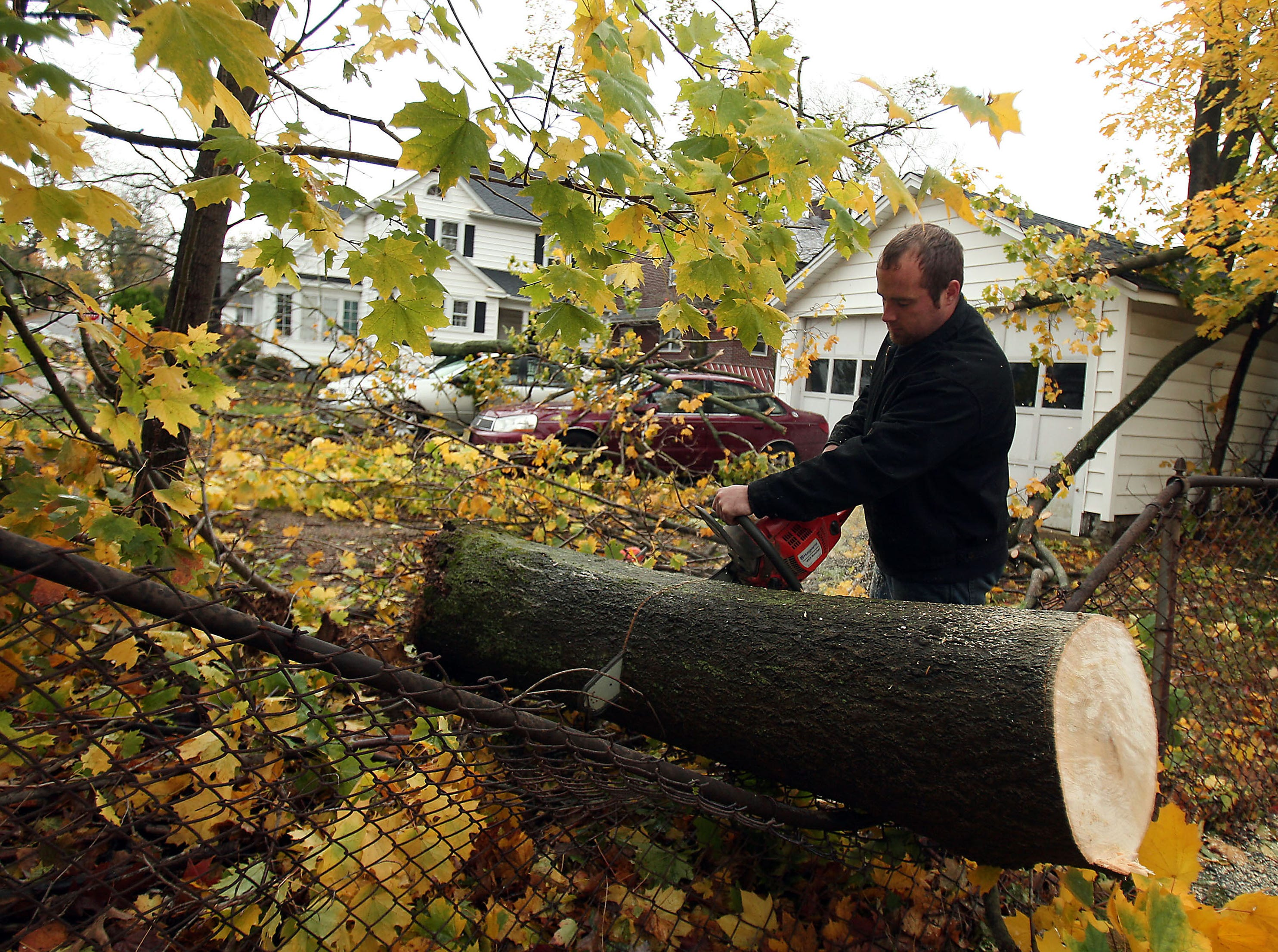 Morristown, NJ-- October 30, 2012--Steve Penzenik of Roxbury uses a chain saw to cut up a fallen tree on Mills Street in Morristown, NJ after Hurricane Sandy left homes damages and without power throughout New Jersey. 