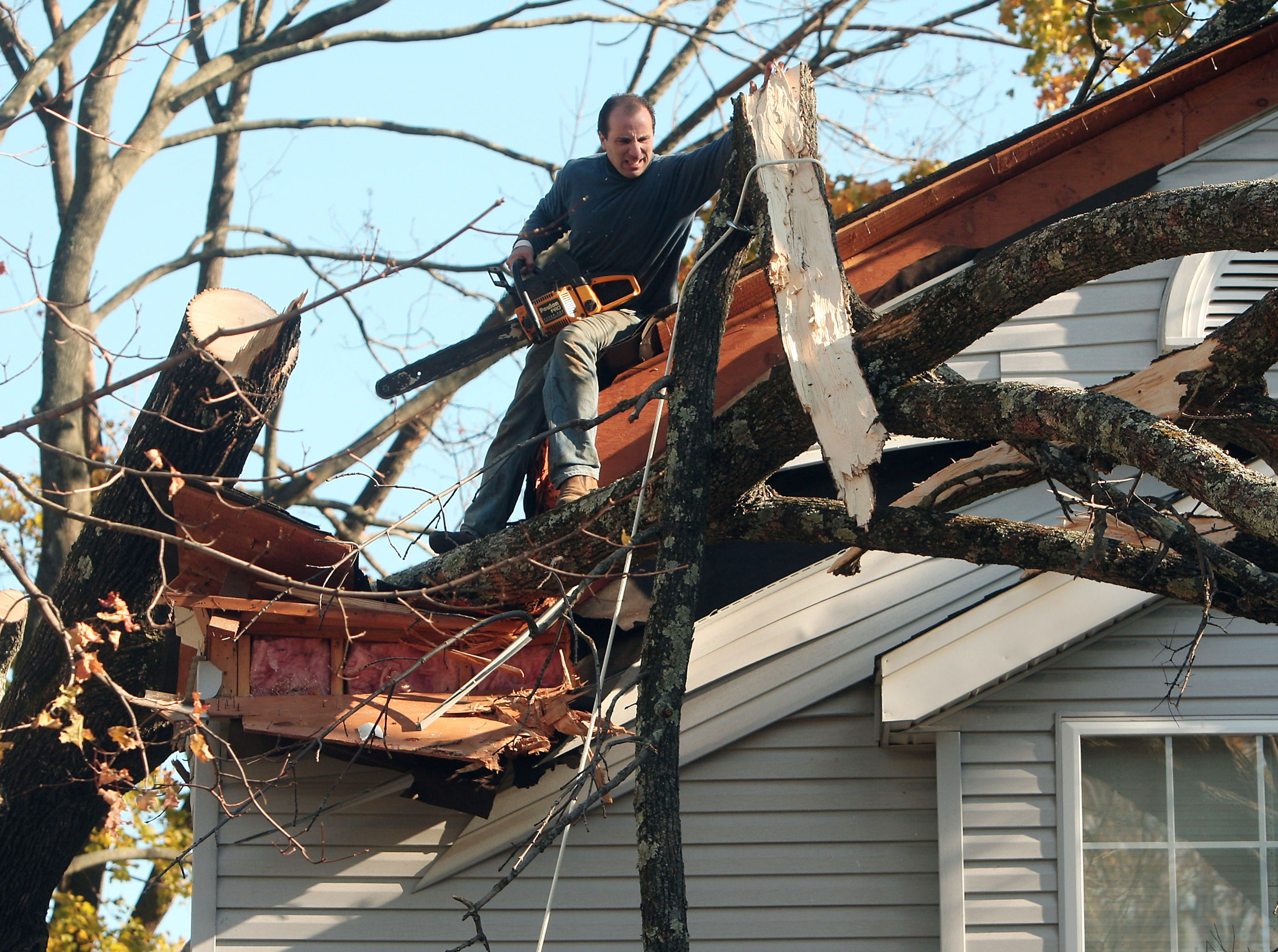 Morristown, N.J.- November 5, 2012--Joe Esposito of HLM Designs in Randolph, NJ take down a large tree that destroyed part of a Morristown homeowners roof during Hurricane Sandy.