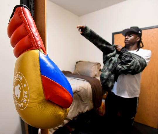 Alabama State University freshman Ivry Hall, of Chicago, dresses in his dorm room, as his boxing gloves hang on the a cabinet door, on the ASU campus in Montgomery, Ala. on Monday August 20, 2018.