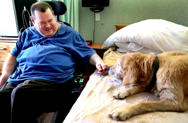J.T. Potts, a resident at Community Care of Rutherford County, gives a treat to Goldie, the rehabilitation center's dog, in his room on Thursday, Oct. 25, 2018. Goldie was recently diagnosed with kidney failure, and Potts wrote a Facebook post in Goldie's voice about her time at Community Cares.