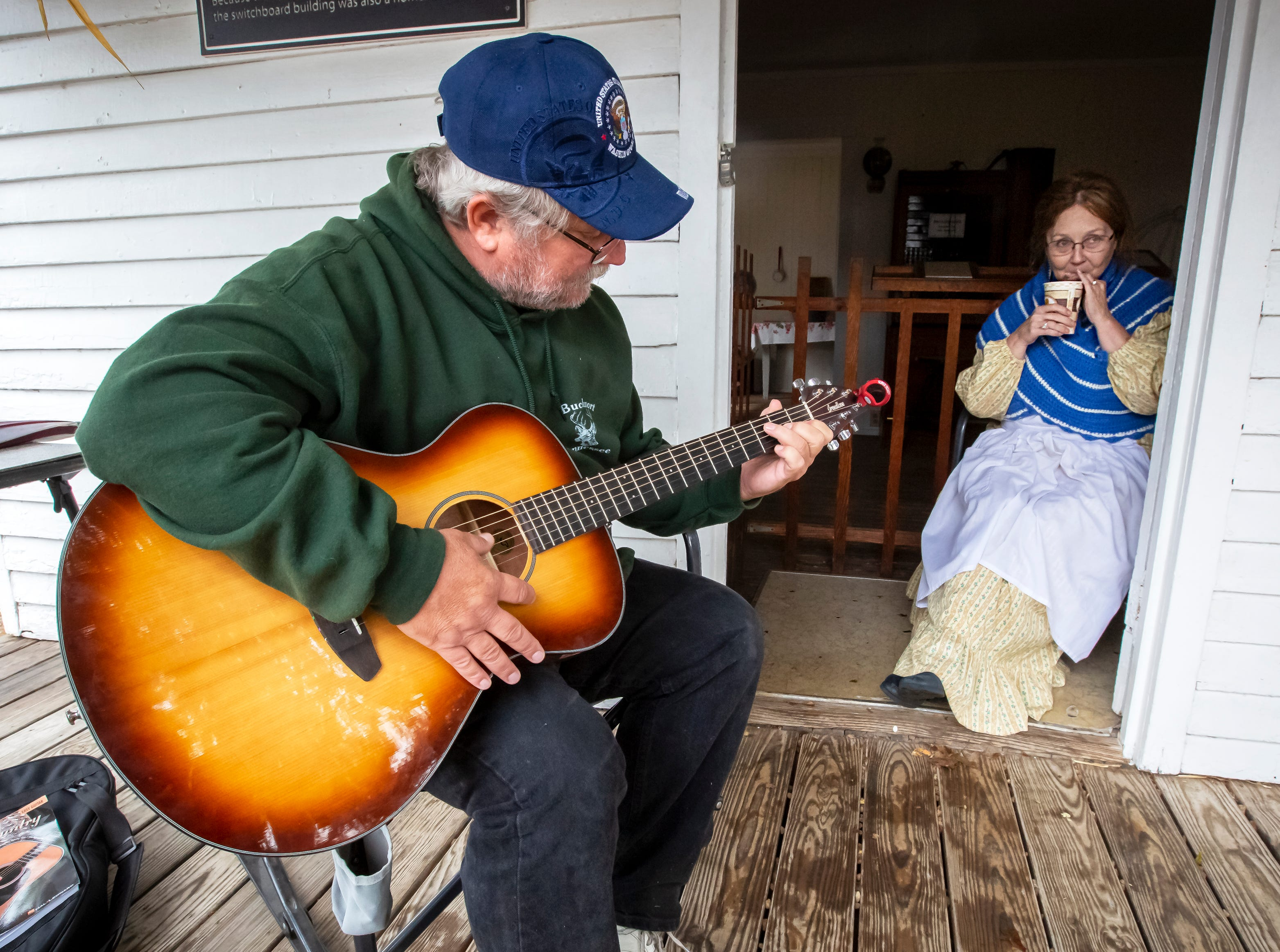 David Roberts plays his guitar the Ginger Jenkins sips her hot chocolate on a damp rainy day at the 43rd annual Harvest Days celebration held at Cannonsburgh Villiage.