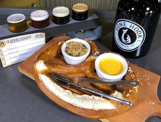 The Jumbo Bavarian Pretzel starter is served with Honey Hole beer cheese and stone-ground mustard at the new Bone Hook Brewing Co. in North Naples.