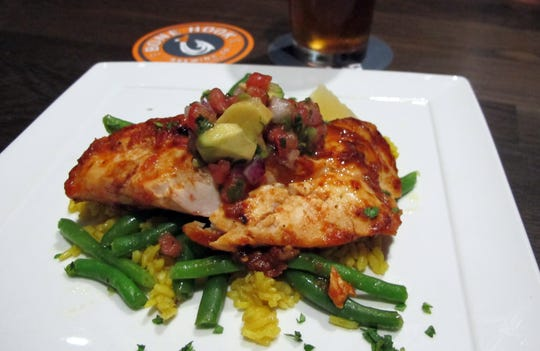 Chipotle Rubbed Mahi served with avocado salsa over yellow rice and fresh green beans is one of the menu favorites at the new Bone Hook Brewing Co. in North Naples.