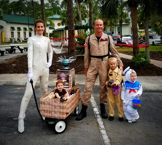 "Lauren Osborne shared this photo of her family's costume theme for Halloween. Lauren writes: ""My daughter wanted to be a Ghostbuster for Halloween. I'm Gozer. My husband, Philip, is a Ghostbuster. Raelyn, 4, is also a Ghostbuster. My son Myles, 2, is the Stay Puft Marshmallow Man. My daughter Isla Belle, 9 months old, is one of Gozer's terror dogs and to transport her around, I transformed a wagon into Gozer's Temple."""