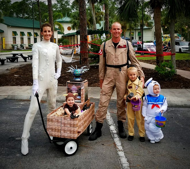 """Lauren Osborne shared this photo of her family's costume theme for Halloween. Lauren writes: """"My daughter wanted to be a Ghostbuster for Halloween. I'm Gozer. My husband, Philip, is a Ghostbuster. Raelyn, 4, is also a Ghostbuster. My son Myles, 2, is the Stay Puft Marshmallow Man. My daughter Isla Belle, 9 months old, is one of Gozer's terror dogs and to transport her around, I transformed a wagon into Gozer's Temple."""""""