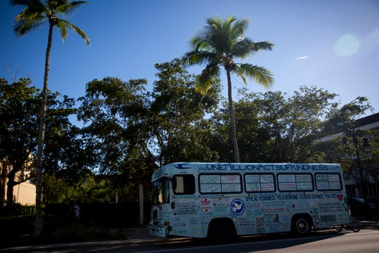 Bob Votruba's One Million Acts of Kindness bus, which is covered in messages, is parked along the street while he talks to people walking by on Thursday, Oct. 25, 2018, on Fifth Avenue South in Naples.