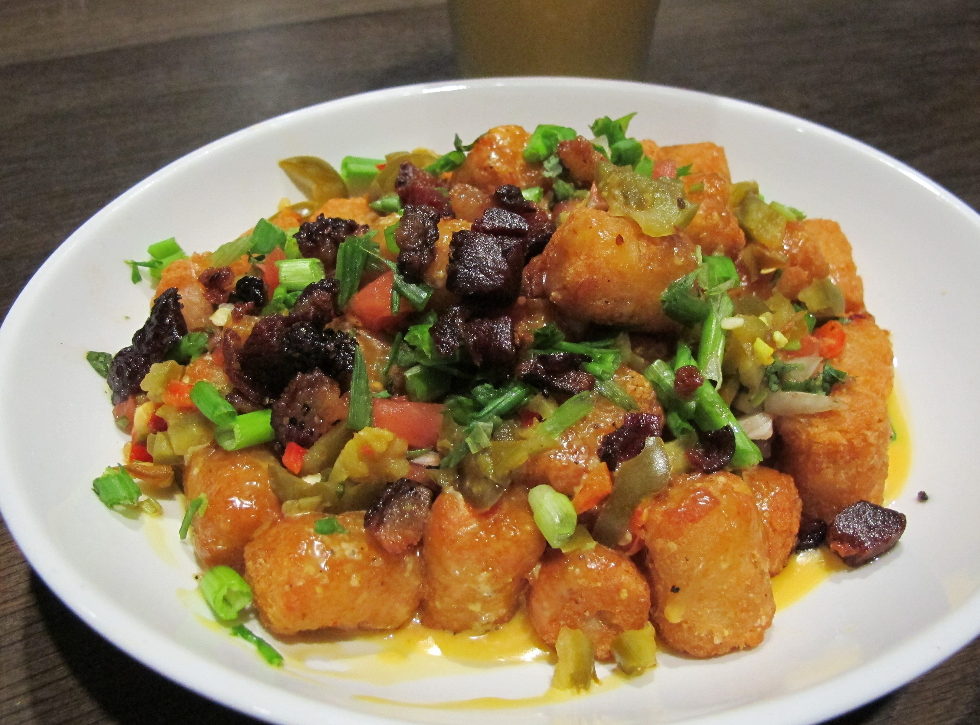 Loaded Tator Tots with bacon chunks, beer cheese, green onions, peppers and pico de gallo is one of the favorites on the menu of the new Bone Hook Brewing Co. in North Naples.