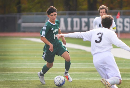 Matthew O'Shea (no.14) of Ramapo (in green) makes his way as Kevin Woodard (no.3) of West Milford (in white) blocks him during the second half for the first round of the North 1, Group 3 tournament, at Ramapo High School field in Franklin Lakes on 10/29/18.  Ramapo won the game 6 to 1 over West Milford.