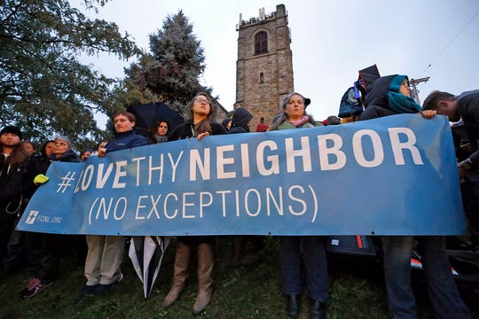 A group holds a sign in the Squirrel Hill section of Pittsburgh during a vigil for the victims of the Tree of Life Synagogue shooting Saturday, Oct. 27, 2018.