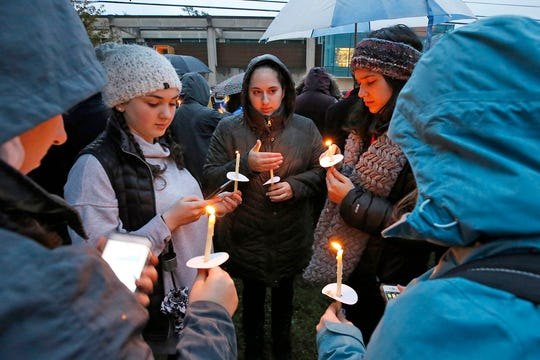 Holding candles, a group of girls wait for the start of a memorial vigil in the Squirrel Hill section of Pittsburgh for the victims of the shooting at the Tree of Life Synagogue.