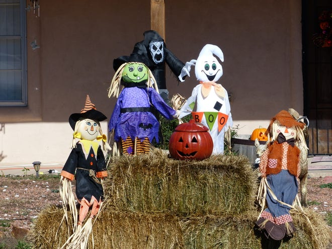 A ghoul lurks behind a band of assorted Halloween characters on a lawn near Sierra Vista Primary in Ruidoso.