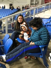 Emily Moutzouros (left), of Northville, enjoys Sunday's Sensory Friendly Game with sons Nate, 5, and Alex, 11. Alex has autism.