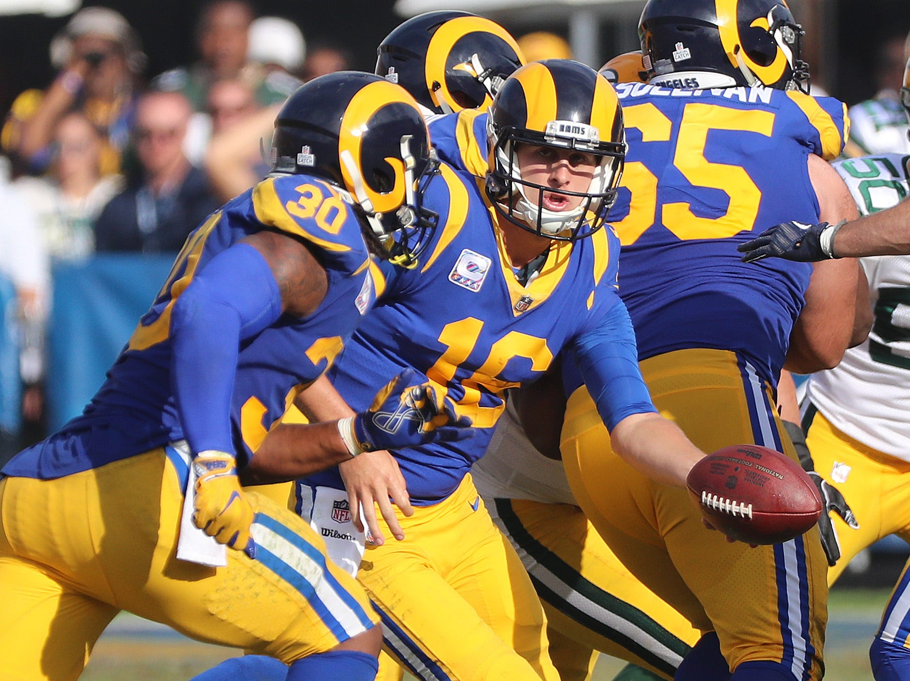 Los Angeles Rams quarterback Jared Goff (16) hands off to running back Todd Gurley (30) against the Green Bay Packers Sunday, October 28, 2018 at the Memorial Coliseum in Los Angeles.