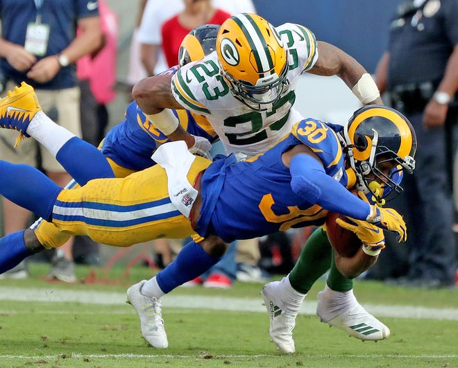 Green Bay Packers cornerback Jaire Alexander (23) tackles running back Todd Gurley (30) against the LA Rams Sunday, October 28, 2018 at the Memorial Coliseum in Los Angeles.