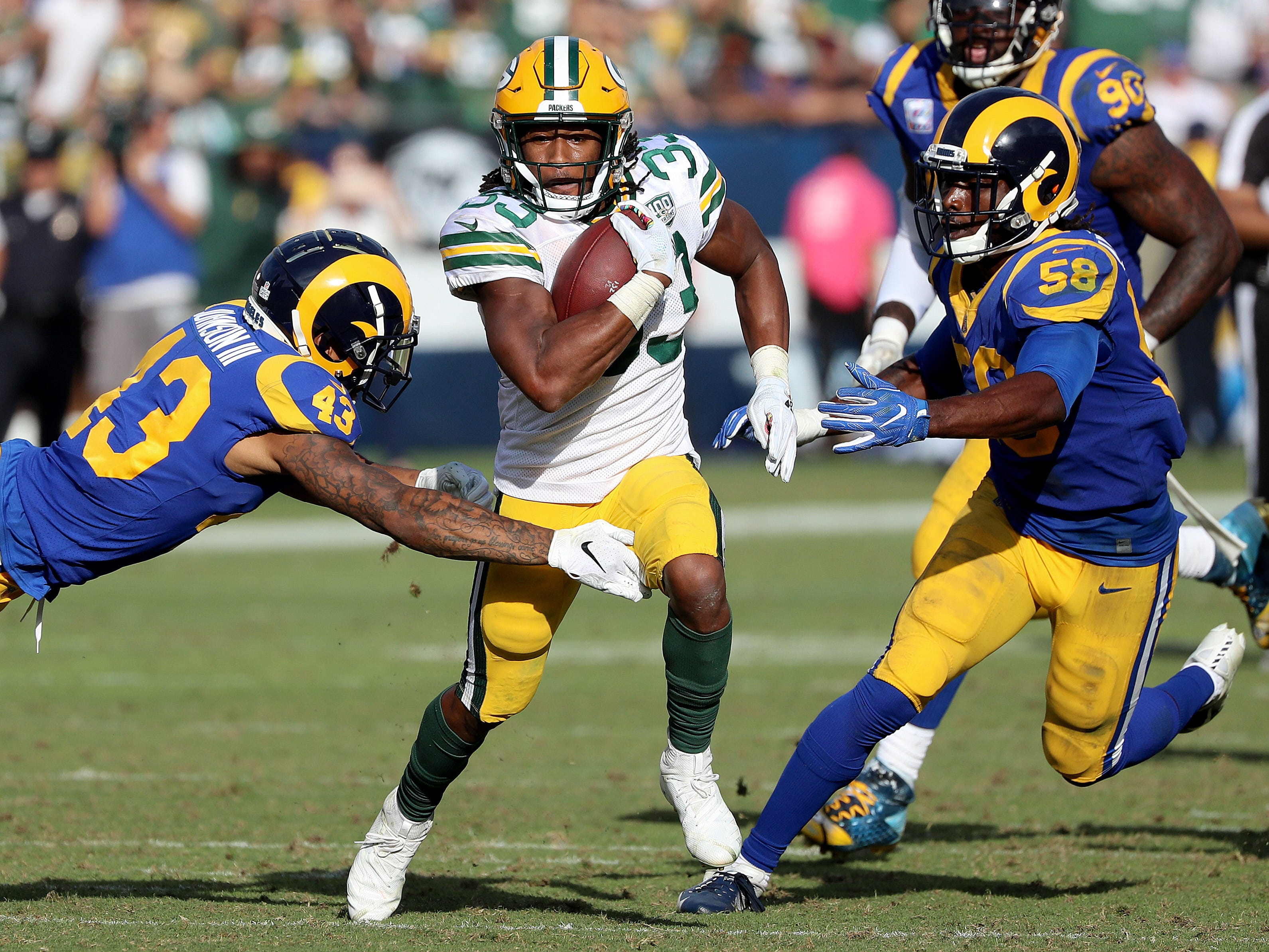 Green Bay Packers running back Aaron Jones (33) splits defenders linebacker Cory Littleton (58) and strong safety John Johnson (43) on a long touchdown run against the LA Rams Sunday, October 28, 2018 at the Memorial Coliseum in Los Angeles.