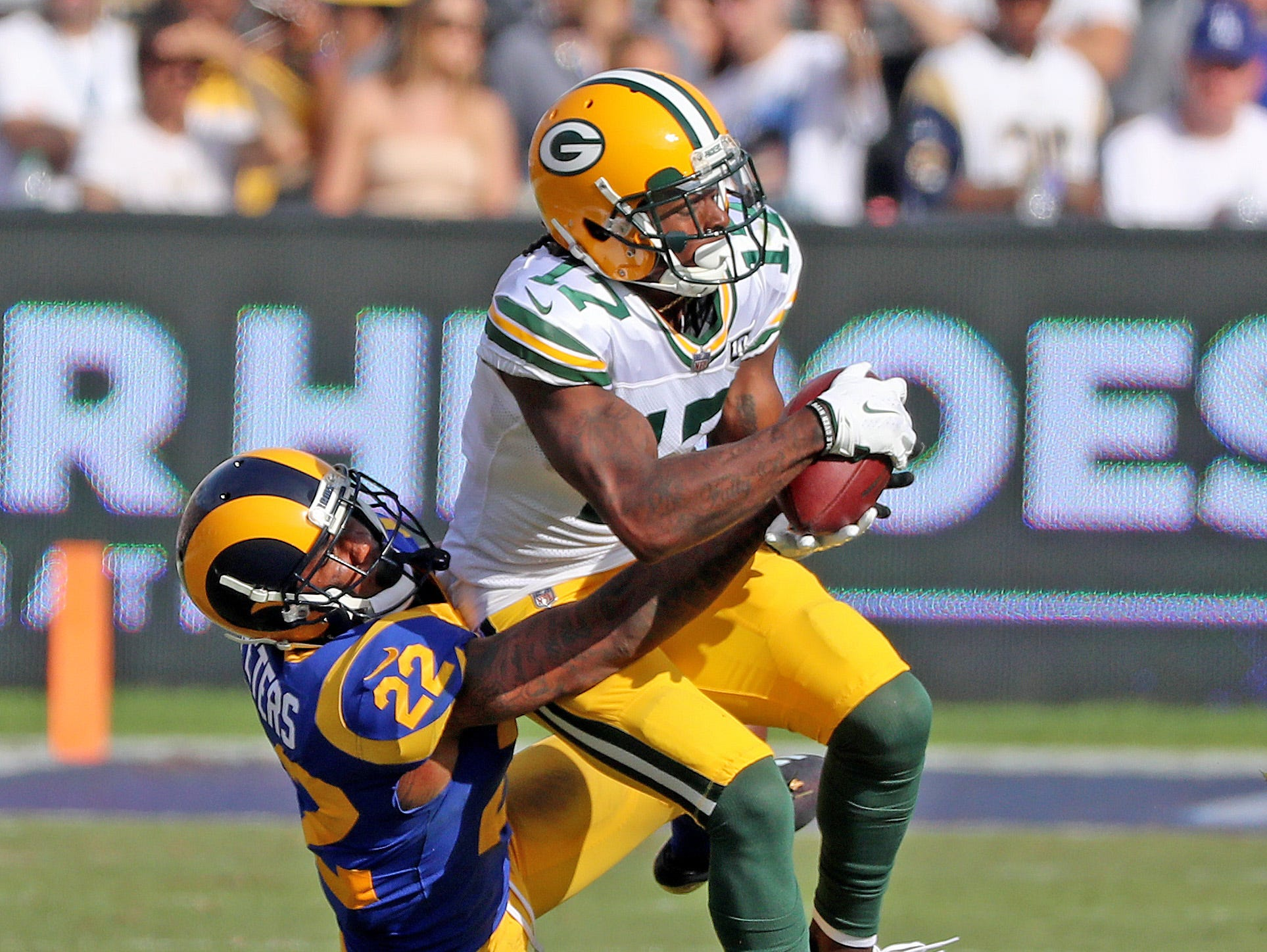 Green Bay Packers wide receiver Davante Adams (17) gets thrown down after a catch against cornerback Marcus Peters (22) of the LA Rams Sunday, October 28, 2018 at the Memorial Coliseum in Los Angeles.
