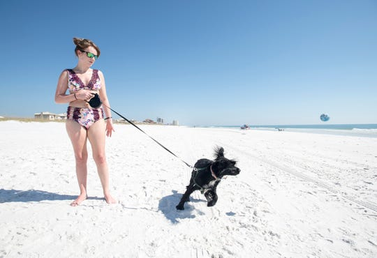 Katlyn Gardner, of Jasper, Alabama, plays fetch with her dog Huck at the dog beach in Pensacola on Monday, October 29, 2018.