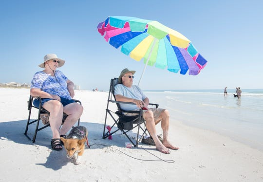 Carole and Mike Coleman, of Springfield, Ohio, sit along the waters edge with their dog Brandy at the dog beach in Pensacola on Monday, October 29, 2018.
