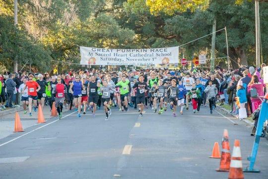 Runners break through the starting line at a previous Great Pumpkin Run.