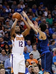 Oct 28, 2018; Oklahoma City, OK, USA; Phoenix Suns forward TJ Warren (12) shoots as Oklahoma City Thunder guard Alex Abrines  (right) defended during the second quarter at Chesapeake Energy Arena. Mandatory Credit: Alonzo Adams-USA TODAY Sports
