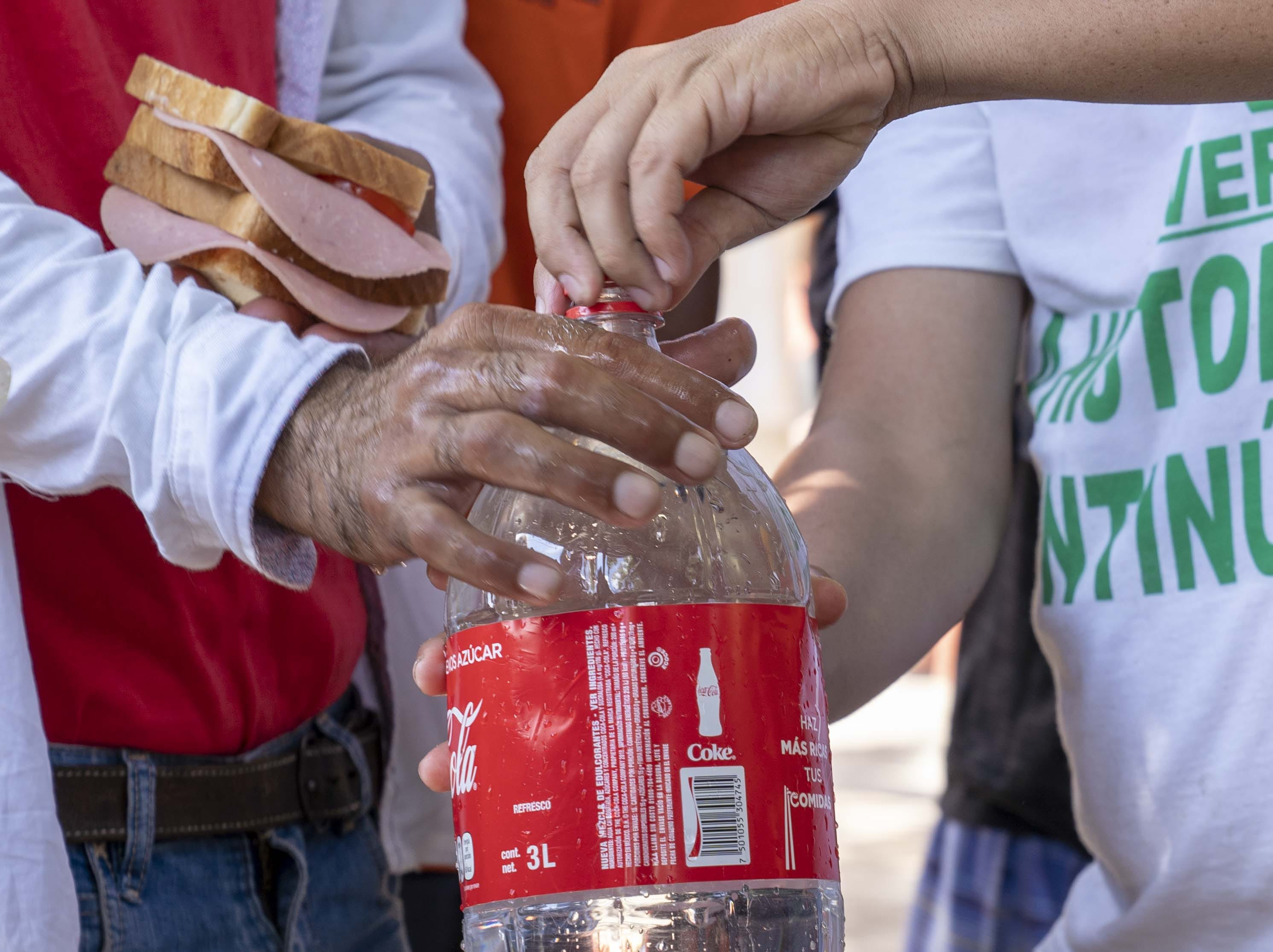 Migrants feeling water in a coke bottle. The thousands of migrants from Honduras and other Central American countries traveling in a huge caravan toward the U.S. took a day off to rest on Sunday, Oct. 28, 2018.