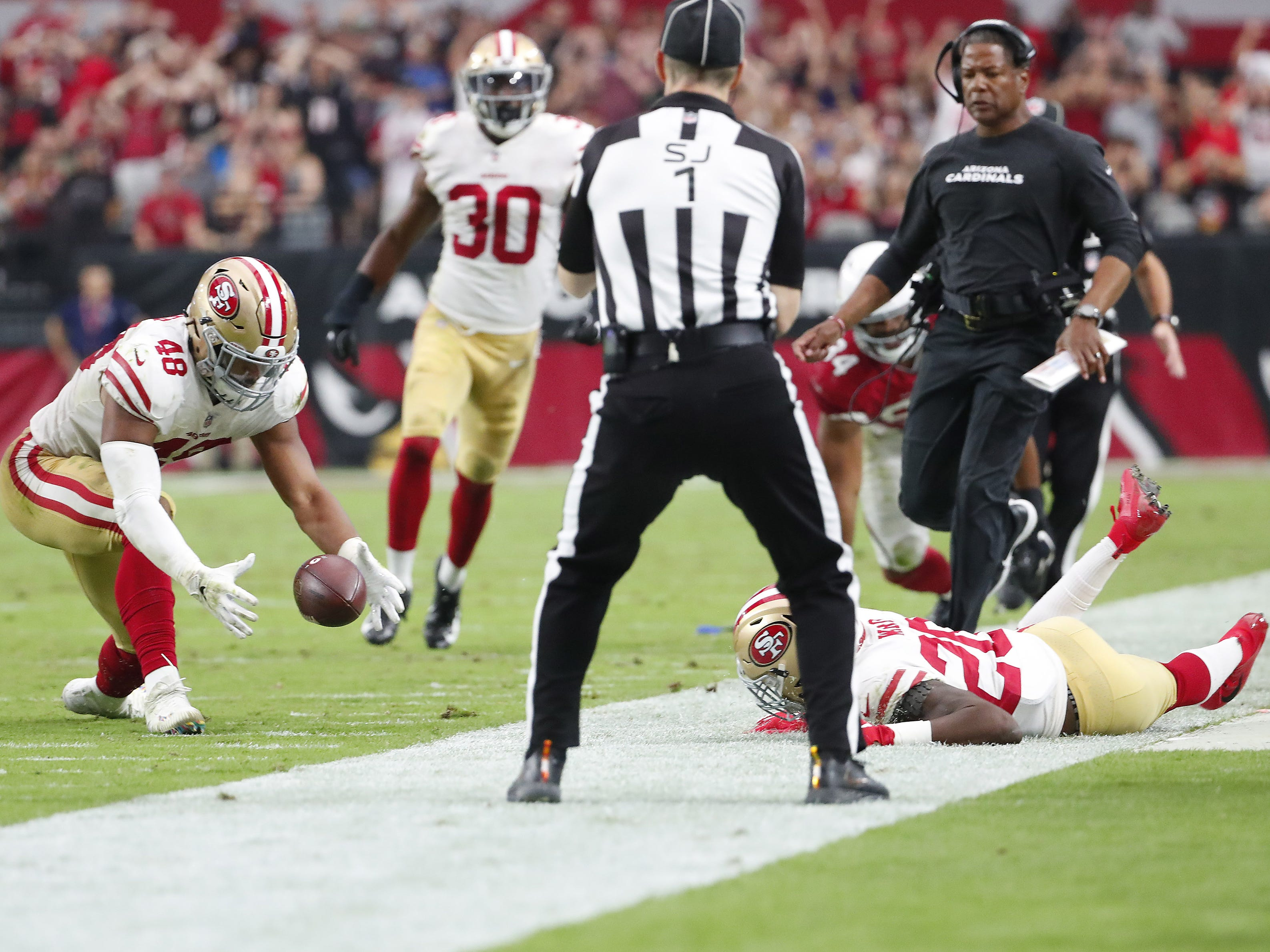 San Francisco 49ers linebacker Fred Warner (48) recovers a fumble against the Arizona Cardinals in the fourth quarter during NFL action on Oct. 28 at State Farm Stadium.