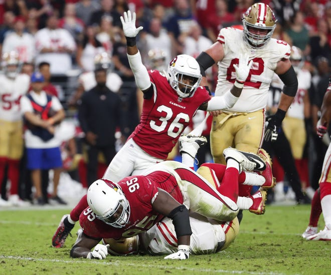 Arizona Cardinals defensive tackle Rodney Gunter (95) sacks San Francisco 49ers quarterback C.J. Beathard (3) as strong safety Budda Baker (36) celebrates in the fourth quarter on Oct. 28 at State Farm Stadium.