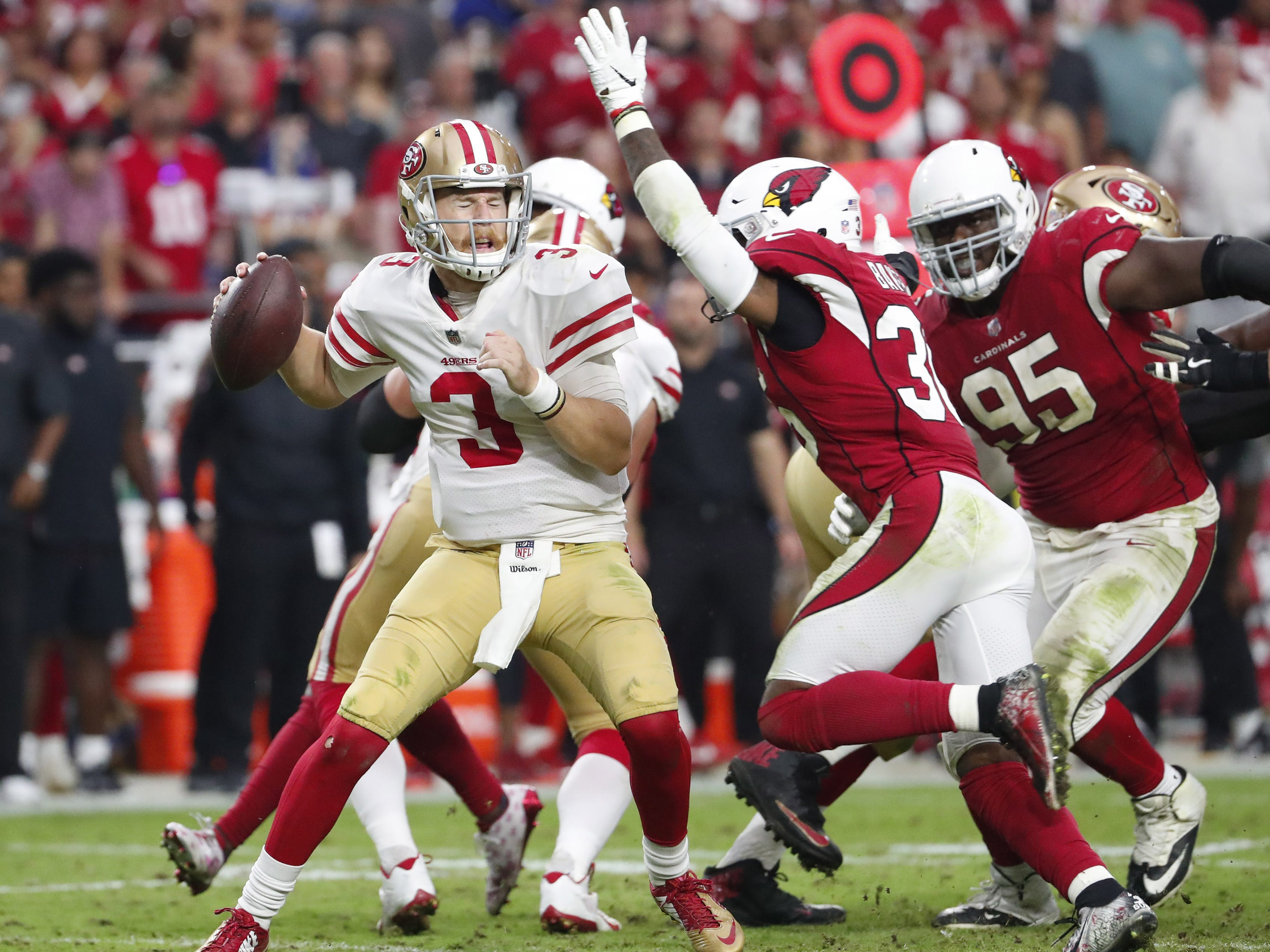 San Francisco 49ers quarterback C.J. Beathard (3) braces for a hit by Arizona Cardinals strong safety Budda Baker (36) in the fourth quarter during NFL action on Oct. 28 at State Farm Stadium.
