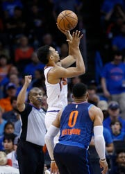 Phoenix Suns guard Elie Okobo, left, shoots in front of Oklahoma City Thunder guard Russell Westbrook (0) in the second half of an NBA basketball game in Oklahoma City, Sunday, Oct. 28, 2018. (AP Photo/Sue Ogrocki)