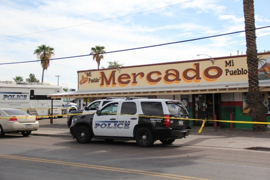 Police tape surrounds the market in Mesa where the dead body of a man was found Oct. 29, 2018.