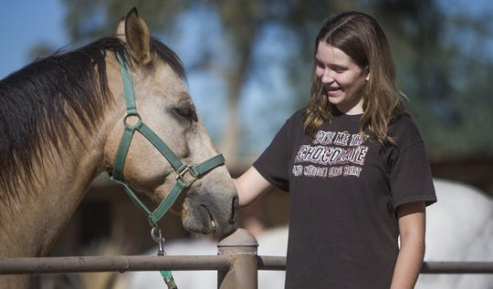 "Devon Lortie, 13, pets ""Rango"" at Hunkapi Farms in Scottsdale, during a program that allows students with autism-spectrum disorder to interact with horses at the farm."