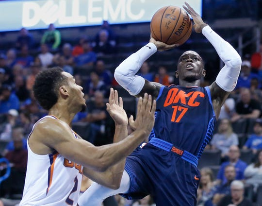 Oklahoma City Thunder guard Dennis Schroder (17) shoots in front of Phoenix Suns guard Elie Okobo (2) in the second half of an NBA basketball game in Oklahoma City, Sunday, Oct. 28, 2018. (AP Photo/Sue Ogrocki)