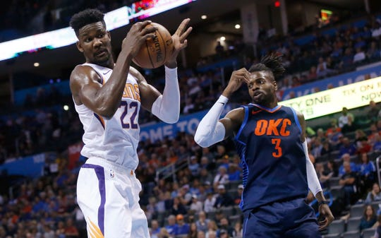 Phoenix Suns center Deandre Ayton (22) grabs a rebound in front of Oklahoma City Thunder forward Nerlens Noel (3) in the second half of an NBA basketball game in Oklahoma City, Sunday, Oct. 28, 2018. (AP Photo/Sue Ogrocki)