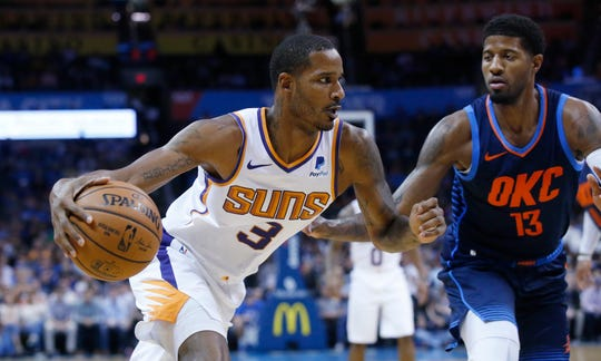 Suns forward Trevor Ariza drives around Thunder forward Paul George during the first half of a game on Oct. 28.