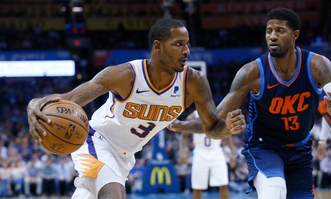 Phoenix Suns forward Trevor Ariza (3) drives around Oklahoma City Thunder forward Paul George (13) in the first half of an NBA basketball game in Oklahoma City, Sunday, Oct. 28, 2018. (AP Photo/Sue Ogrocki)