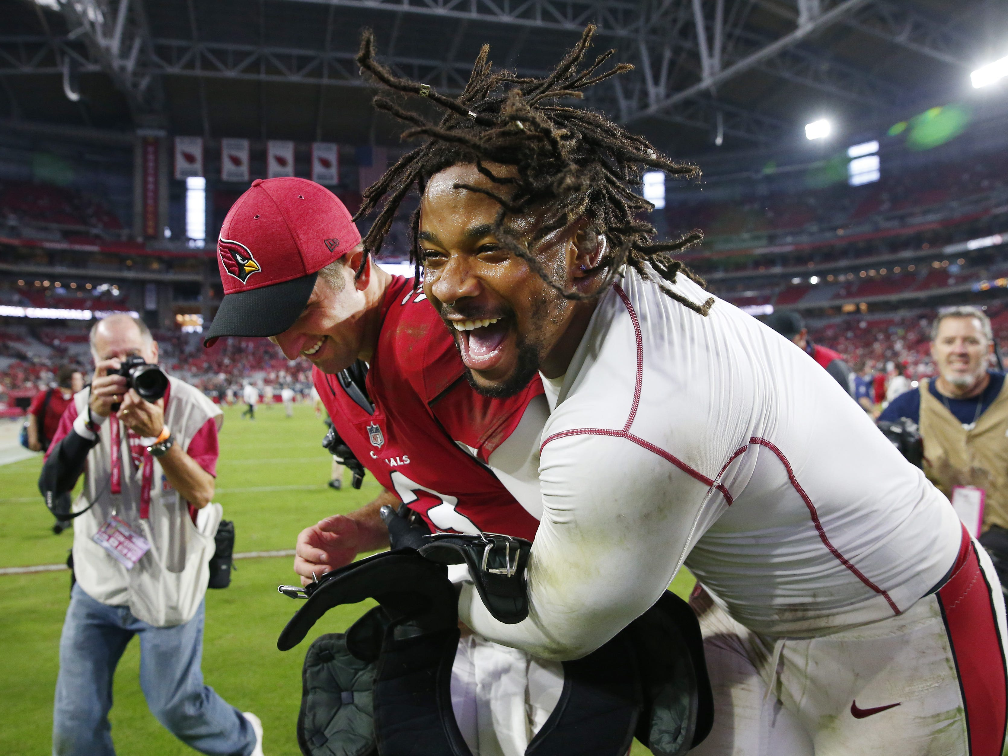Arizona Cardinals quarterback Josh Rosen (left) is hugged by defensive tackle Robert Nkemdiche (90) after an 18-15 come-from-behind win against the San Francisco 49ers on Oct. 28 at State Farm Stadium.