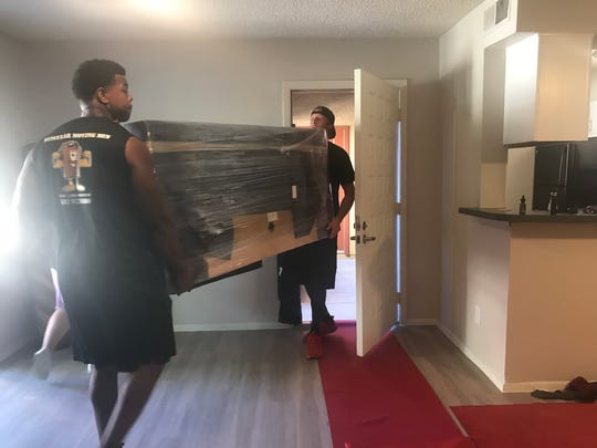 Muscular Moving Men crew leaders James Watts (left) and Mike Gidson (right) carry living room furniture into the Rosales family's new apartment. The company donated its services after learning the family had to find a new home suddenly.