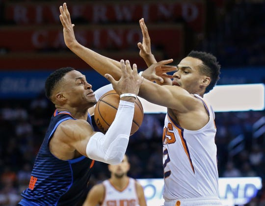Oklahoma City Thunder guard Russell Westbrook, left, loses control of the ball after a foul by Phoenix Suns guard Elie Okobo, right, in the second half of an NBA basketball game in Oklahoma City, Sunday, Oct. 28, 2018. (AP Photo/Sue Ogrocki)