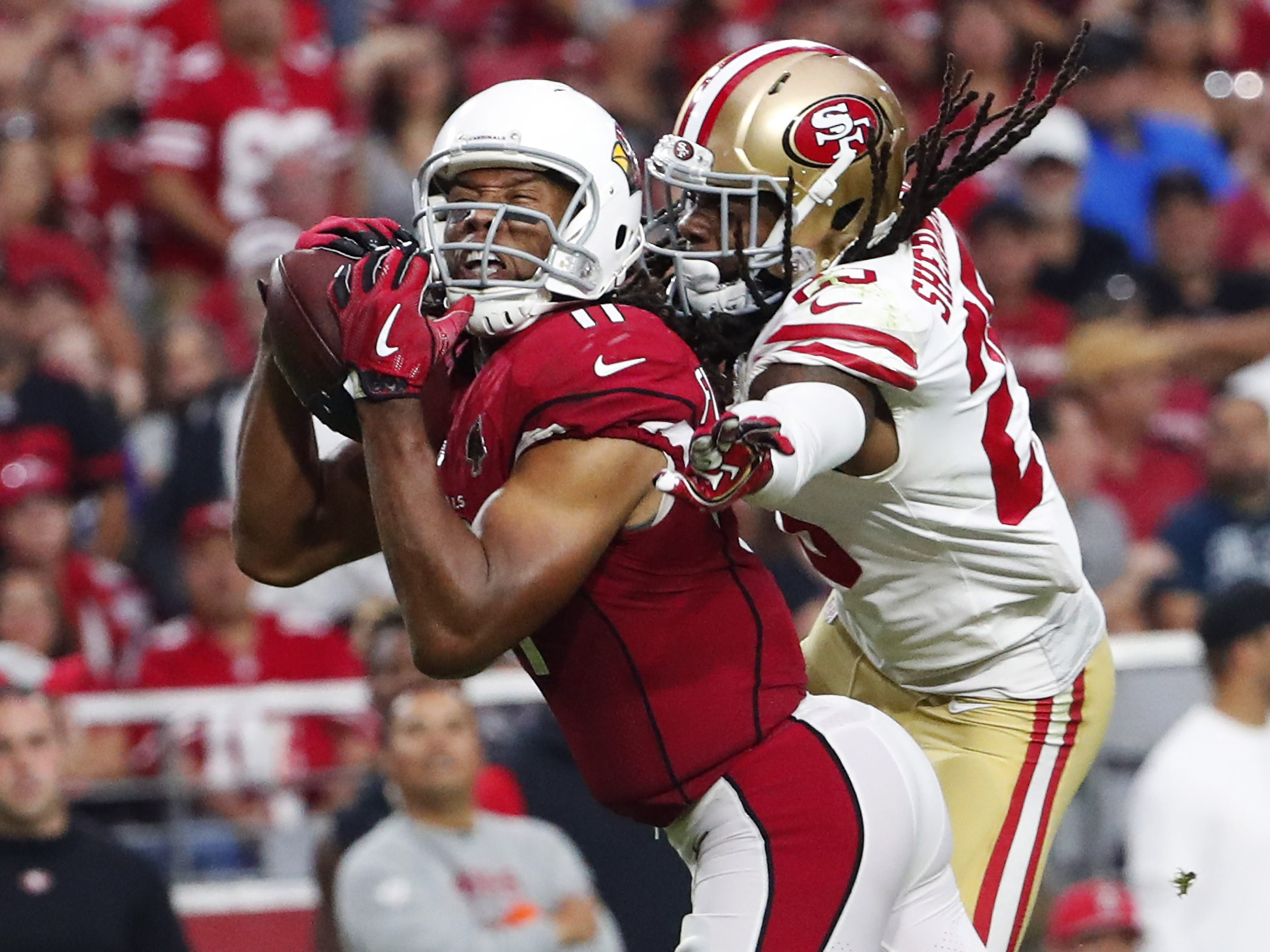 Arizona Cardinals wide receiver Larry Fitzgerald (11) catches a pass against San Francisco 49ers cornerback Richard Sherman (25) in the fourth quarter during NFL action on Oct. 28 at State Farm Stadium.