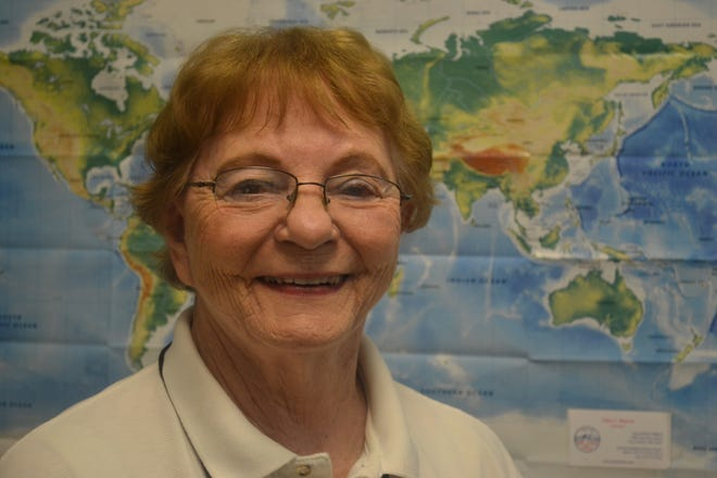 Edna Hansen, Port Clinton city treasurer, stands in front of a map in her office. Hansen said her ability to fly, and her membership with Ninety-Nines, gave her the opportunity to travel to places she had never visited.