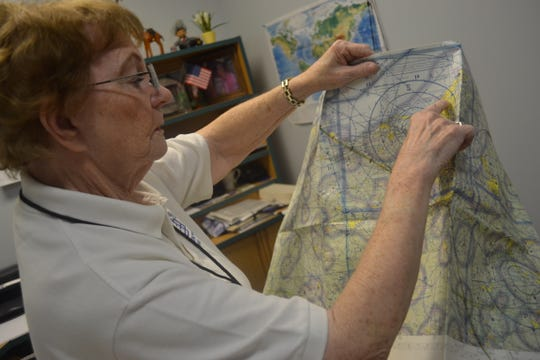 Edna Hansen points to a location on the flight map she used as a pilot. Hansen became a member of the Ninety-Nines when she earned her pilot's license in 1979.