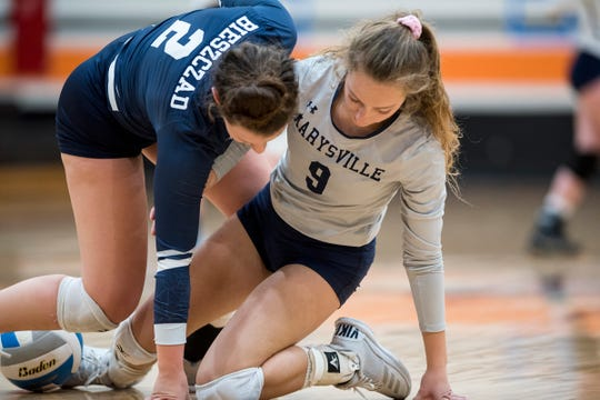 Marysville High School's Abigail Sawdon (9) and Tyler Bieszczad help each other up after running into each other chasing the ball during their Division 2 girls volleyball game against Algonac High School Monday, Oct. 29, 2018 at Armada High School.