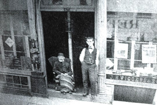 Howard T. Wiggers, right, stands in front of Wiggers Toy and Sporting Goods Store on Main Street in Poughkeepsie as the store's founder and Wiggers's grandfather, John Henry, sits next to him.